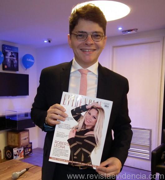 O anfitrião exibindo a revista Evidência Cosmopolita no lançamento do seu livro